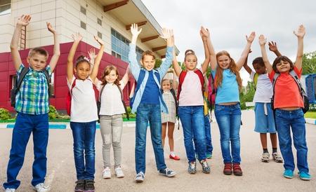 Gelukkige kinderen met de armen omhoog staan in de buurt schoolgebouw in de zomer dagen tijd