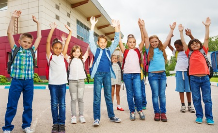 in row: Niños felices con los brazos arriba de pie cerca de edificio de la escuela durante el tiempo de día de verano