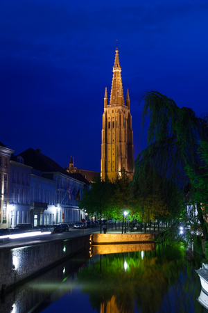 church of our lady: Church of Our Lady Bruges at night from the canal, Bruges, Belgium Stock Photo