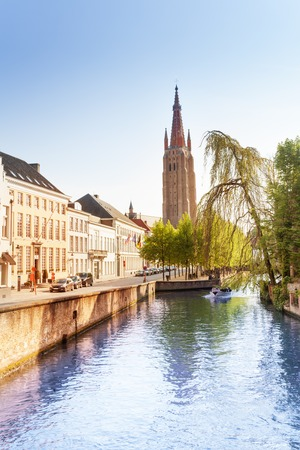 our lady: Beautiful Church of Our Lady Bruges view from river canal during summer in Belgium