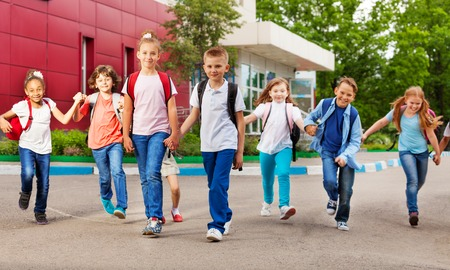 children hands: Row of happy kids with bags near school building walking holding hands during summer day time recess