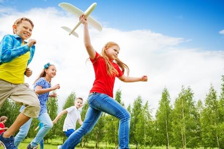 niños felices: Vista desde abajo de la muchacha que sostiene el juguete avión blanco grande y los niños detrás corriendo en el campo durante el día de verano Foto de archivo