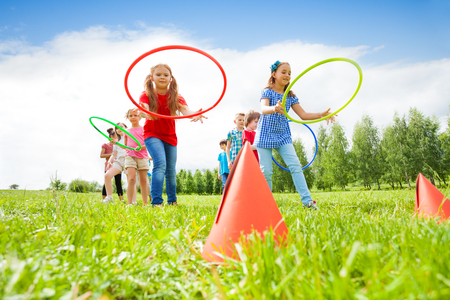 kinderen: Gelukkig meisjes en jongens in kleurrijke kleding gooien kleurrijke hoepels op kegels, terwijl de concurrentie met elkaar tijdens de zomer zonnige dag