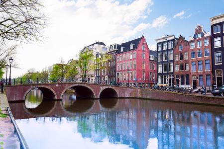ladrillo: Vista de canal de Amsterdam con el r�o y las casas durante el verano con el cielo nublado Foto de archivo