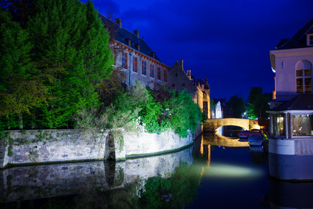 historical reflections: Dijver with historical buildings reflections in river during night in Bruges, Belgium