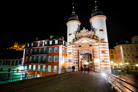 alte: Gates and towers on Alte Brucke bridge during night time in Heidelberg, Germany
