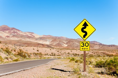 curved: Road with arrow yellow sign in desert, California, United States