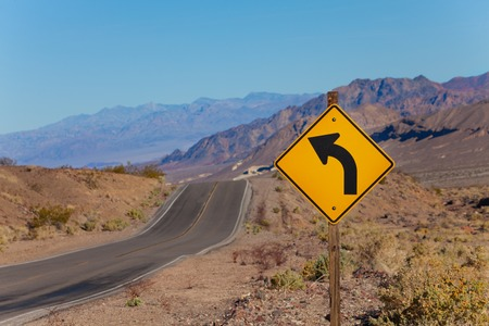 Road with curved arrow yellow sign in desert, California, United States Stock Photo