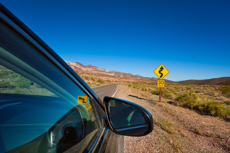 stopped: Car stopped on the road with arrow yellow sign in desert, California, United States Stock Photo