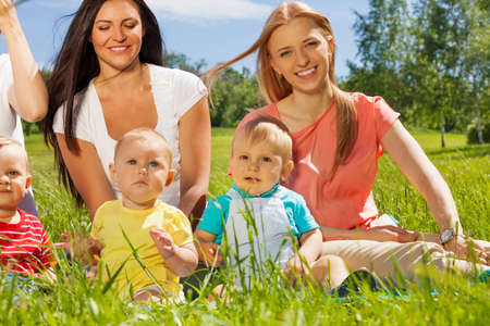Happy mothers with their babies sitting together on the green grass during wonderful summer day photo