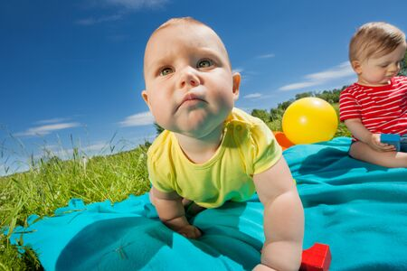 Cute baby crawling and other one sitting on blanket in the field during sunny summer day photo