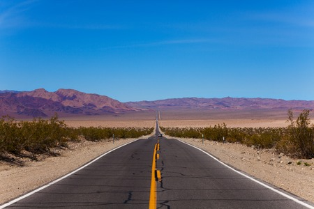 Cracked road with lines during day time in desert, California, United States