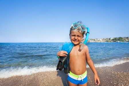 scuba mask: Boy with scuba mask and paddles stands on the seashore squinting against the sun