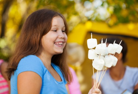 Fat kid: Positive cute girl holds sticks with marshmallow sitting near yellow tent with her friends during sunny autumn day on the campsite