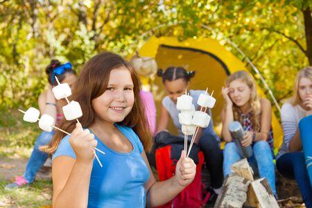 niños sentados: La muchacha sostiene los palillos con la melcocha sentado cerca de la tienda de color amarillo con sus amigos durante el día soleado de otoño en el camping