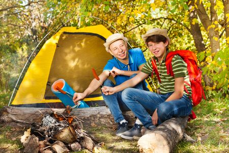 teen boys: Teen boys sit on campsite with sausages sticks near fireplace with yellow tent during autumn day in the forest