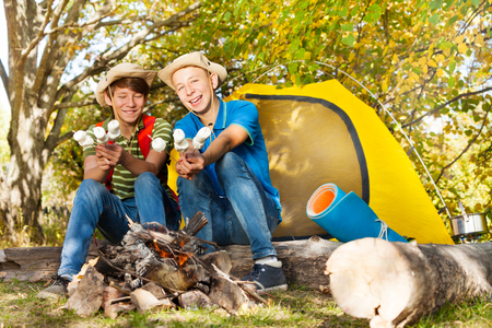 hot boy: Two boys with hats hold marshmallow sticks near fireplace with yellow tent during autumn day in the forest