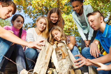 International teens construct bonfire together near yellow tent during autumn day in the forest