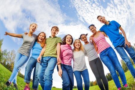 niños riendose: Amigos de risa de diversidad de pie en la hierba en la fila en el parque durante el día soleado de otoño en fondo del cielo Foto de archivo