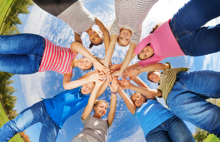View from below of teens standing in star shape with arms together on sky background during sunny day