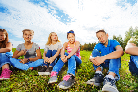sky and grass: Smiling international friends sitting together on grass in park during sunny autumn day Stock Photo