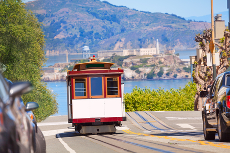 san francisco: Hyde street and San Francisco tram during summer sunny day with Alcatraz island on background, San Francisco, USA