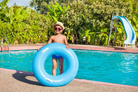 slide glass: Smiling boy in hat and sunglasses holds blue  inflatable ring standing near the swimming pool outside in summer