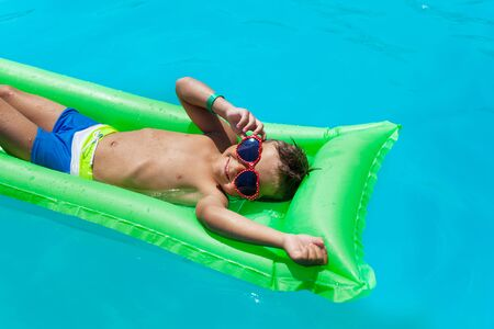 swimming: Boy with sunglasses relaxing on green inflatable mattress in swimming pool during summer Stock Photo
