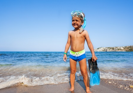 paddles: Boy with scuba mask, paddles standing on the seashore squinting against the sun