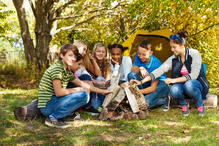 adventure holiday: Happy teens setting up bonfire together on campsite during sunny autumn day in forest