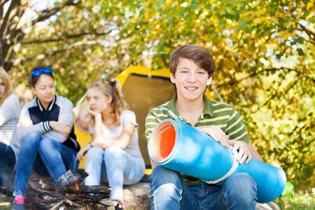 spandex: Happy boy holding blue rolled spandex mat sitting near camping place with her friends Stock Photo
