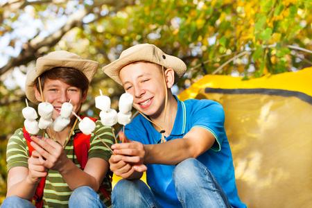 帽子ハッピーボーイズ フォレスト内秋の日の間に黄色のテントが付いている暖炉の近くのマシュマロ棒を保持します。 写真素材