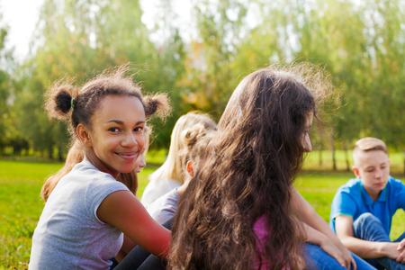Adolescents internationales heureux assis ensemble sur le pré vert pendant merveilleuse journée d'automne ensoleillée
