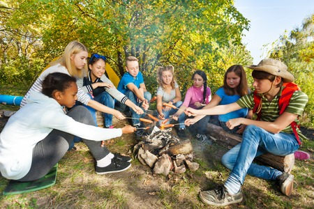 Teens grilling sausages on campsite sitting near yellow tent during autumn day in the forest Stockfoto