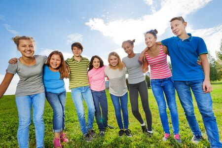 mid teens: Smiling diversity friends standing on grass in row in park during sunny autumn day on sky background