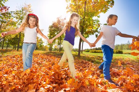 kids outside: Happy kids play holding hands in the park together during beautiful sunny day