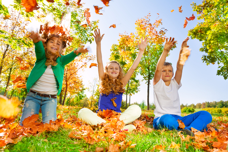 children at play: Children throw and play with leaves in the forest together during beautiful autumn sunny day