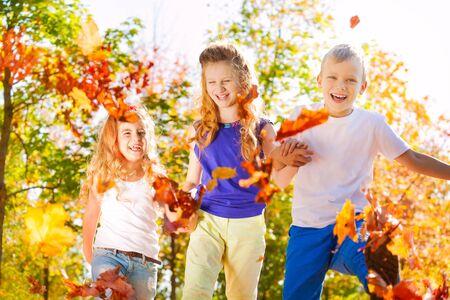 niños riendose: Amigos de risa de la mano en el bosque juntos durante otoño hermoso día soleado Foto de archivo