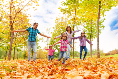 forest park: Happy family with three kids running in the autumn park with stretched hands playing airplane