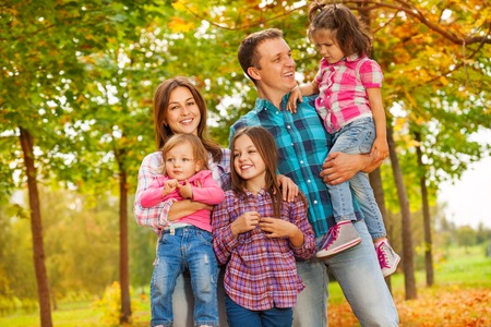 family fall: Happy family in the autumn park holding young daughters Stock Photo