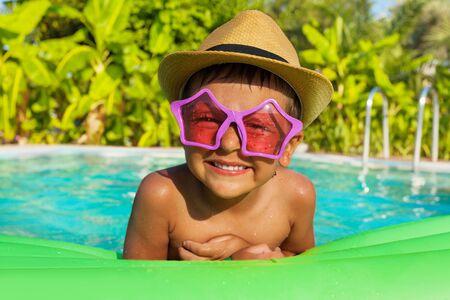 lindo: Ni�o en gafas de sol en forma de estrella en verde airbed en la piscina exterior en verano