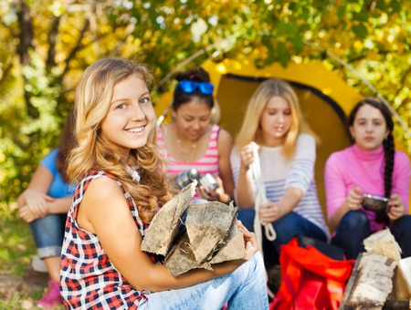 kindling: Happy blonde beautiful girl holding kindling wood sitting near yellow tent with her friends during sunny autumn day at campsite