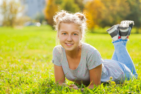 girl legs: Girl close-up view laying on green grass in park during sunny autumn day