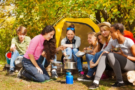 black teens: Teenagers cook soup in metallic pot sitting near yellow tent during autumn day in the forest at the camping site