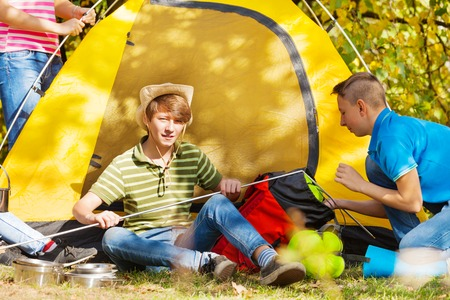 youth group: Boys build yellow tent themselves during autumn day in the forest at the camping site