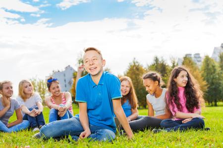 niños riendose: Muchacho de risa y amigos sentados juntos en la pradera verde durante maravilloso día soleado de otoño