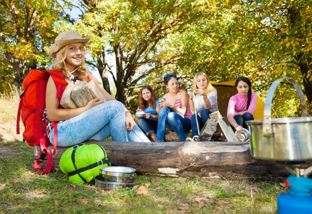 kindling: Blond girl holding kindling wood sitting near bonfire at camping with her friends Stock Photo