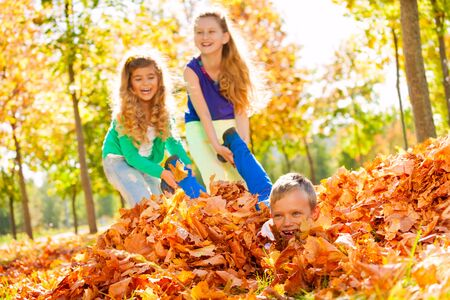 dragging: Girls having fun dragging boy laying on the ground with leaves in forest during beautiful autumn sunny day Stock Photo