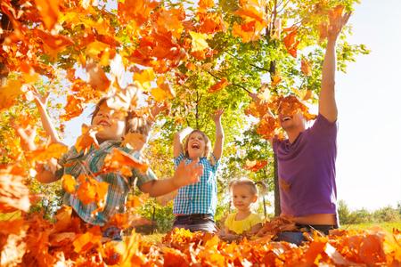 exteriores: Lanzamiento de la familia feliz deja en el aire mientras está sentado en la hierba durante el hermoso día soleado de otoño