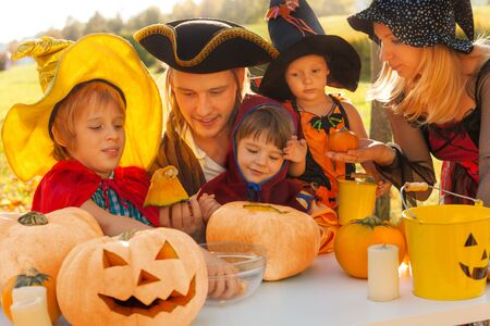Family in pirate and witch costumes crafting Jack-O'-Lantern from pumpkin sitting at the table outside during beautiful sunny autumn day